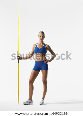 Full length portrait of a young female athlete holding javelin against white background - stock photo