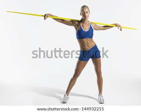 Full length portrait of a young female athlete holding javelin behind shoulders against white background - stock photo