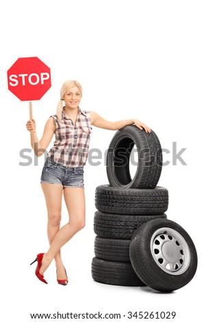 Full length portrait of a young female mechanic posing next to a stack of tires and holding a stop sign isolated on white background - stock photo