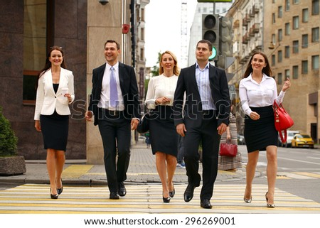Full length portrait of a young Five successful business people crossing the street in the city center - stock photo