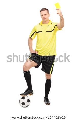 Full length portrait of a young football referee standing over a football and showing a yellow card isolated on white background - stock photo