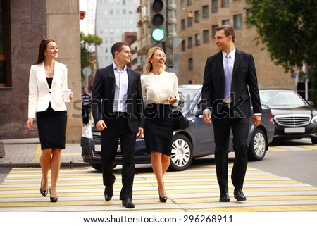 Full length portrait of a young four successful business people crossing the street in the city center - stock photo