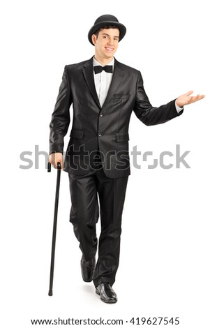 Full length portrait of a young gentleman in a fancy black suit walking with cane isolated on white background  - stock photo