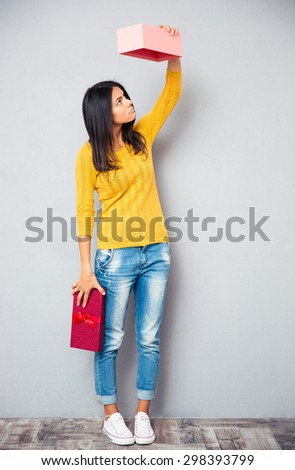 Full length portrait of a young girl holding empty gift box on gray background - stock photo