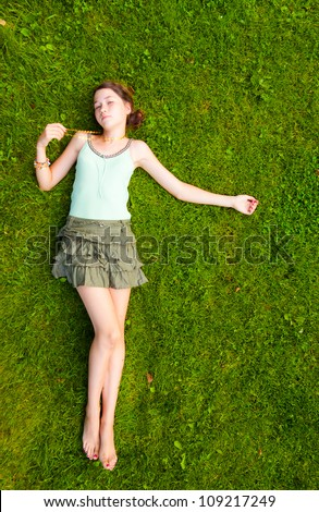 Full length portrait of a young girl lying down on grass in the park - stock photo