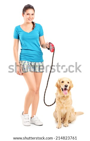 Full length portrait of a young girl walking a dog isolated on white background