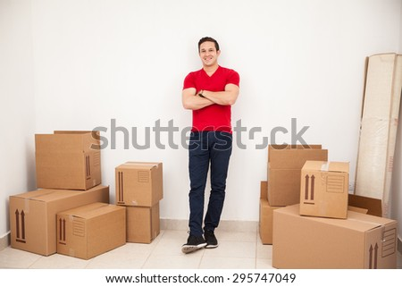Full length portrait of a young handsome man moving into his new home and smiling - stock photo