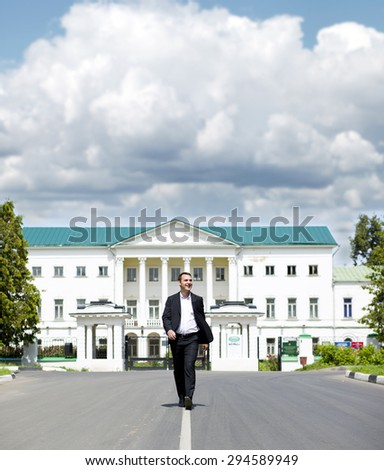 Full length portrait of a young happy businessman walking down the road on the background of summer city - stock photo