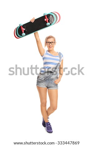 Full length portrait of a young hipster girl holding a skateboard above her head and looking at the camera isolated on white background - stock photo