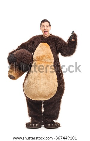 Full length portrait of a young joyful guy in a bear costume giving a thumb up isolated on white background