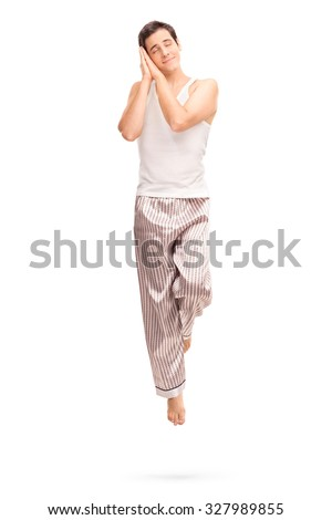 Full length portrait of a young joyful man sleeping and dreaming shot in mid-air isolated on white background