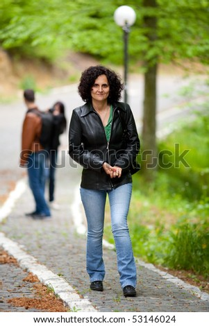 Full length portrait of a young lady walking outdoor in a forest - stock photo