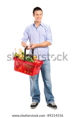 Full length portrait of a young male holding a full shopping basket isolated on white background