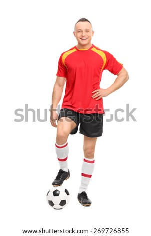 Full length portrait of a young male soccer player standing over a ball and looking at the camera isolated on white background - stock photo
