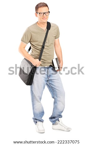 Full length portrait of a young male student holding a book isolated on white background
