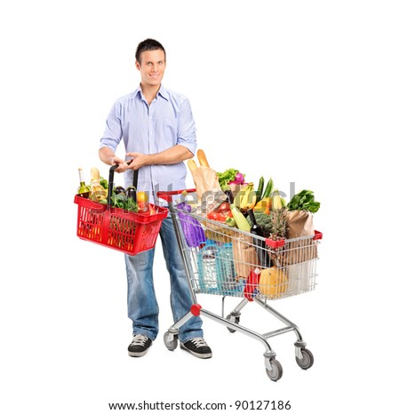 Full length portrait of a young man holding a basket full with products and shopping cart isolated on whte background - stock photo