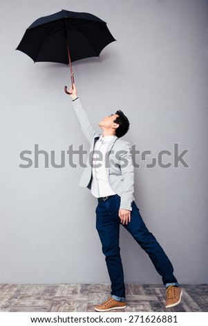Full length portrait of a young man holding umbrella over gray wall - stock photo