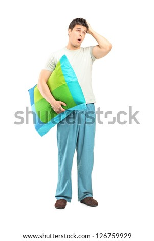 Full length portrait of a young man in pijamas feeling sleepy isolated on white background - stock photo