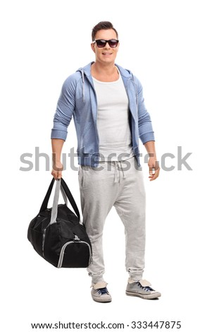 Full length portrait of a young man in sportswear holding a sports bag and pointing to the right with his hand isolated on white background - stock photo