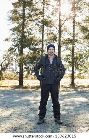 Full length portrait of a young man in warm clothing while having a walk in forest on a winter day - stock photo