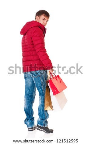 Full length portrait of a young man in winter clothing with shopping bags isolated on white background - stock photo