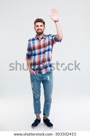 Full length portrait of a young man showing greeting gesture isolated on a white background - stock photo