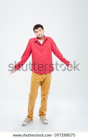 Full length portrait of a young man shrugging shoulders isolated on a white background - stock photo