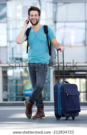 Full length portrait of a young man smiling with suitcase at airport - stock photo