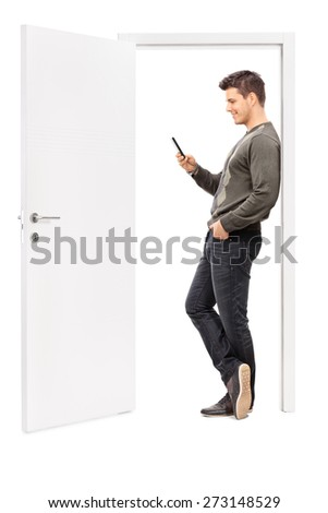 Full length portrait of a young man surfing the net on his cell phone and leaning on the frame of an opened door isolated on white background - stock photo