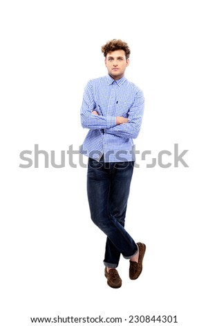 Full length portrait of a young man with arms folded on white background