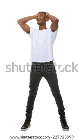 Full length portrait of a young man with hands on head standing on isolated white background - stock photo