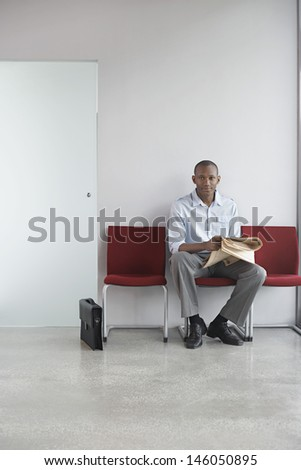 Full length portrait of a young man with newspaper sitting on chair in office corridor - stock photo