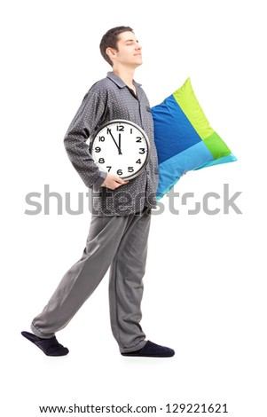 Full length portrait of a young man with pillow and clock sleepwalking isolated on white background - stock photo