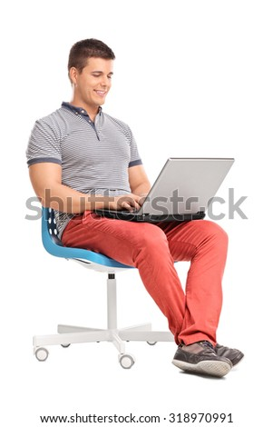 Full length portrait of a young man working on a gray laptop seated on a blue chair isolated on white background