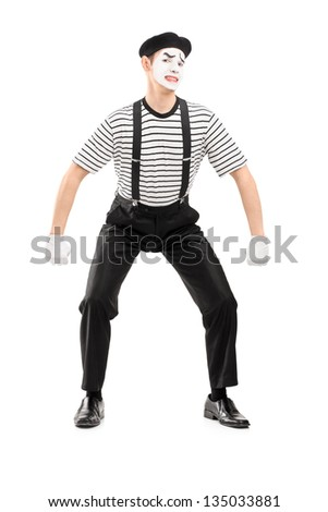 Full length portrait of a young mime artist lifting something imaginary isolated on white background - stock photo