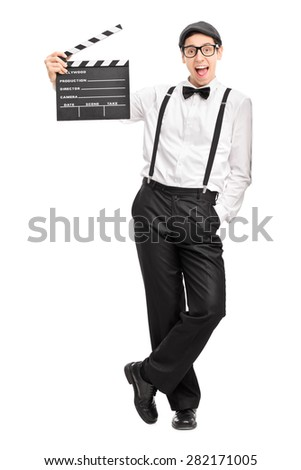 Full length portrait of a young movie director holding a movie clapperboard and leaning against a wall isolated on white background - stock photo
