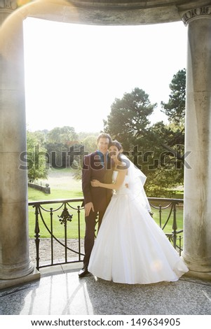 Full length portrait of a young newlywed couple embracing - stock photo