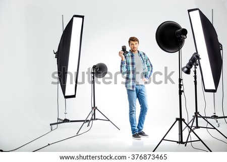 Full length portrait of a young photographer standing with photo camera in studio - stock photo