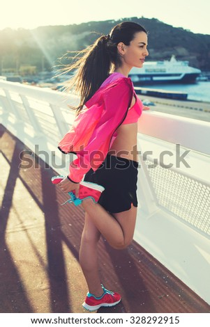 Full length portrait of a young sporty female dressed in colorful bright tracksuit doing stretching exercises for legs, beautiful fit woman engage physical activity outdoors in windy summer evening  - stock photo