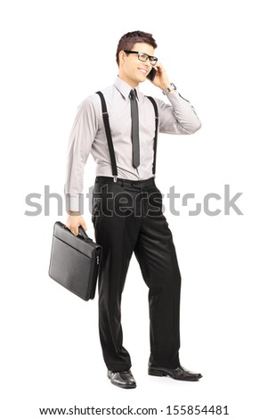 Full length portrait of a young stylish man holding a briefcase and talking on a mobile phone isolated on white background