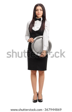 Full length portrait of a young waitress holding a round metal tray and looking at the camera isolated on white background - stock photo