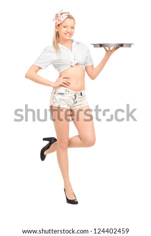 Full length portrait of a young waitress in short pants holding an empty tray isolated on white background - stock photo