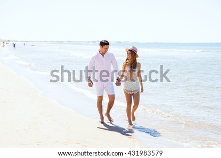 Full length portrait of a young woman and her boyfriend walking down the beach and flirting with each other - stock photo