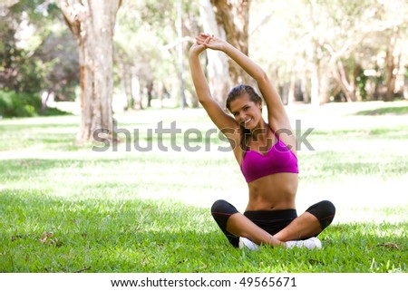 Full length portrait of a young woman doing yoga in an outdoor setting. Horizontal shot. - stock photo