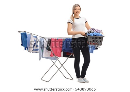 Full length portrait of a young woman holding a laundry basket in front of a clothing rack dryer isolated on white background