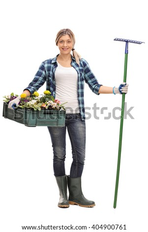 Full length portrait of a young woman holding a rack of flowers and a gardening rake isolated on white background - stock photo