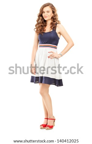 Full length portrait of a young woman in dress posing and looking at camera isolated on white background - stock photo