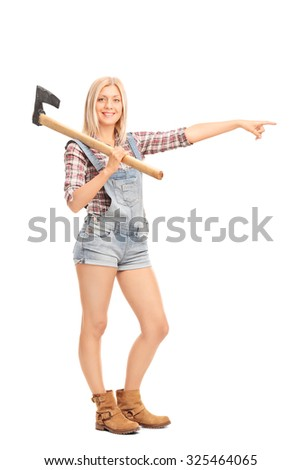 Full length portrait of a young woman in overalls holding an axe and pointing to the right with her hand isolated on white background - stock photo