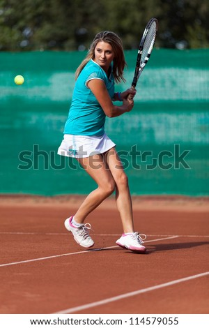 Full length portrait of a young woman playing tennis on a dross field - stock photo