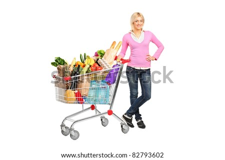 Full length portrait of a young woman posing next to a shopping cart isolated on white background - stock photo